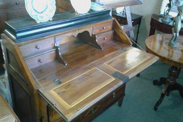 un mobile in legno con dei cassetti e una mensola con due piattini da decorazione