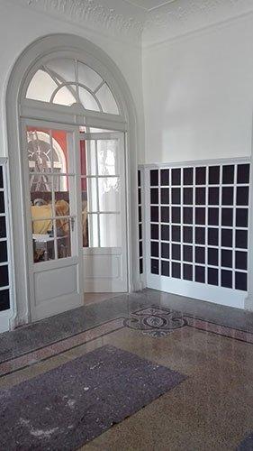 una porta ad arco di color bianco con pannelli di vetro