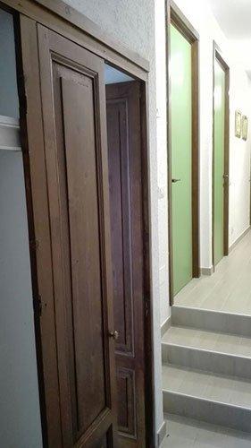 una porta aperta in legno e accanto delle scale