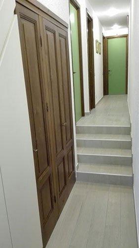 un corridoio e delle porte di color verde