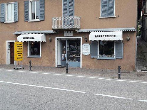 vista dall'esterno di un negozio e due finestre con due tendoni con scritto Antichità'  Tappezziere