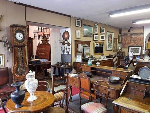 dei mobili in legno di diverso genere all'interno di un antiquario