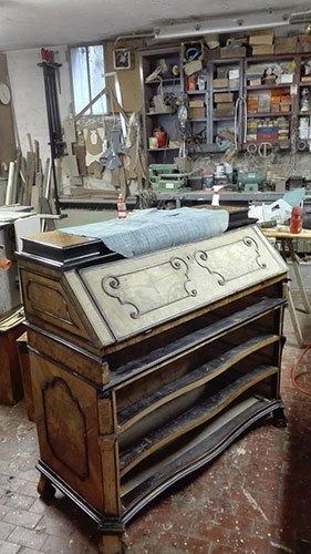 un mobile in legno con dei disegni in una falegnameria
