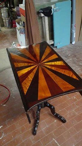 un tavolino in legno con il top di color giallo e bordeaux in una falegnameria