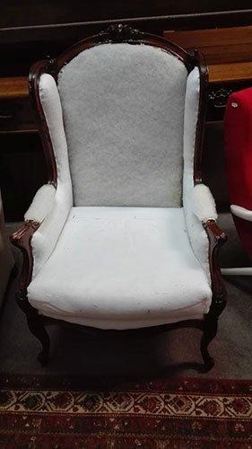 una poltrona in legno con i cuscini di color bianco