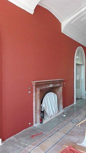 una sala con un camino e un muro dipinto di color rosso