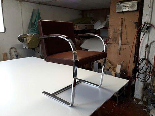 una sedia con cuscini in pelle e una struttura in acciaio inox