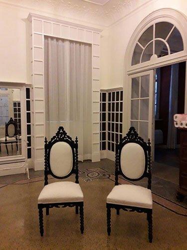 una sala con due sedie di legno con cuscini bianchi