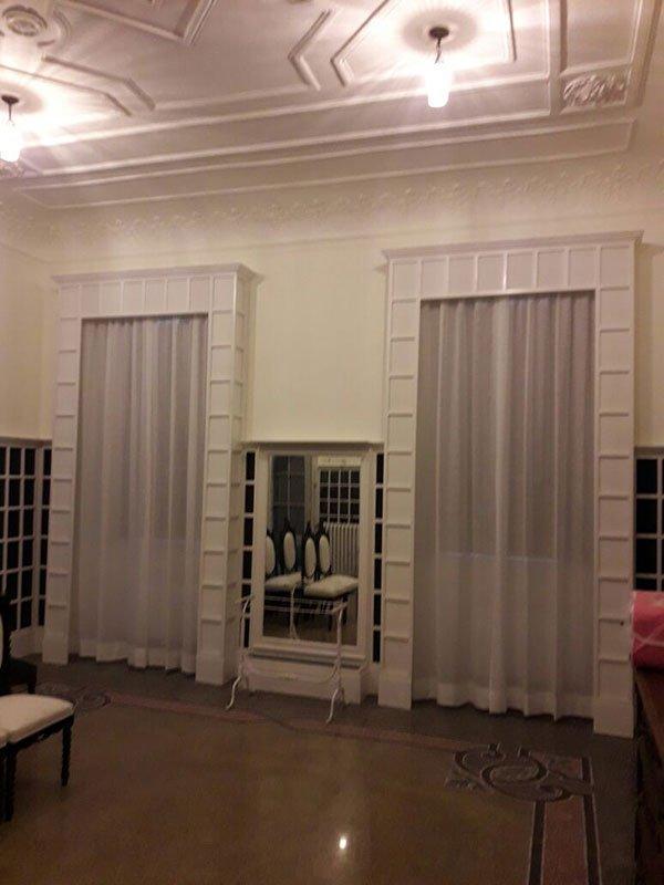 una sala con due finestre con delle tende bianche