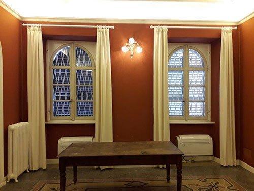 una stanza con due finestre e un tavolino in legno