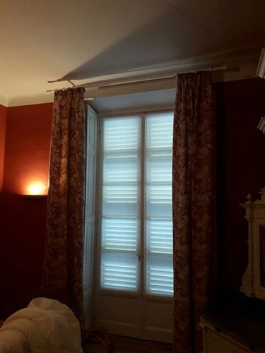 una finestra con delle bianche e di color bordeaux