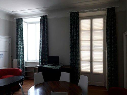 due finestre con delle tende bianche e di color bl