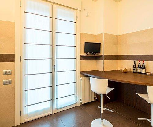 un tavolo a muro in legno e due sgabelli di color bianco