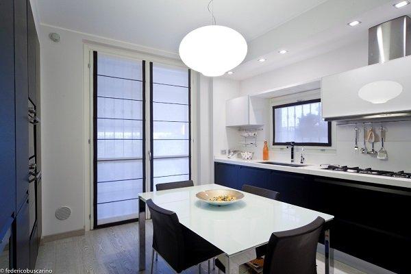 una cucina a blocco di color bianco e nero e una finestra con delle tende a pacchetto