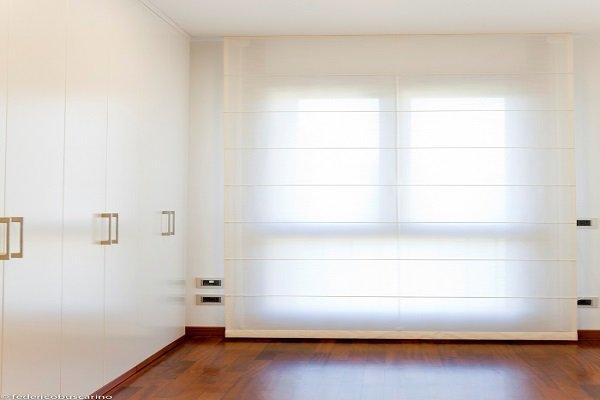 una camera con un armadio e  una finestra con una tenda a pacchetto