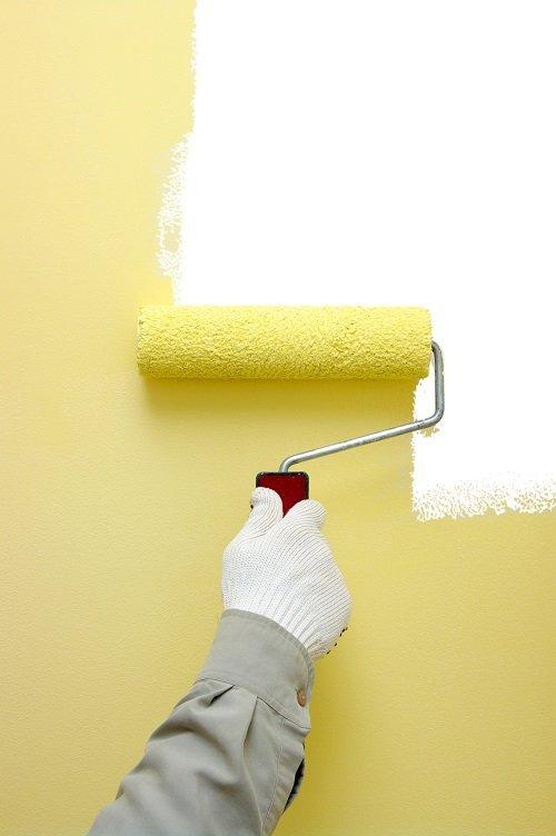 mano che passa un rullo da imbianchino per tingere una parete di giallo