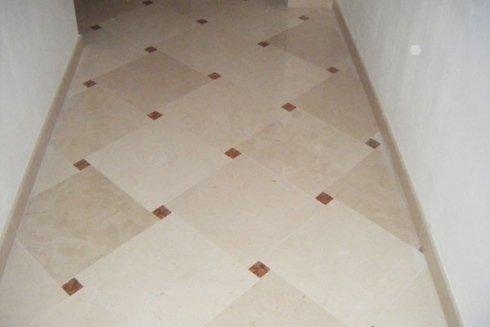 pavimento con superficie lucidata in pietra di apricena e inserti rosso verona