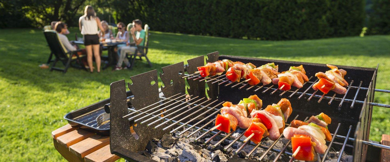 Barbecue con spiedini in giardino con persone al tavolo sullo sfondo