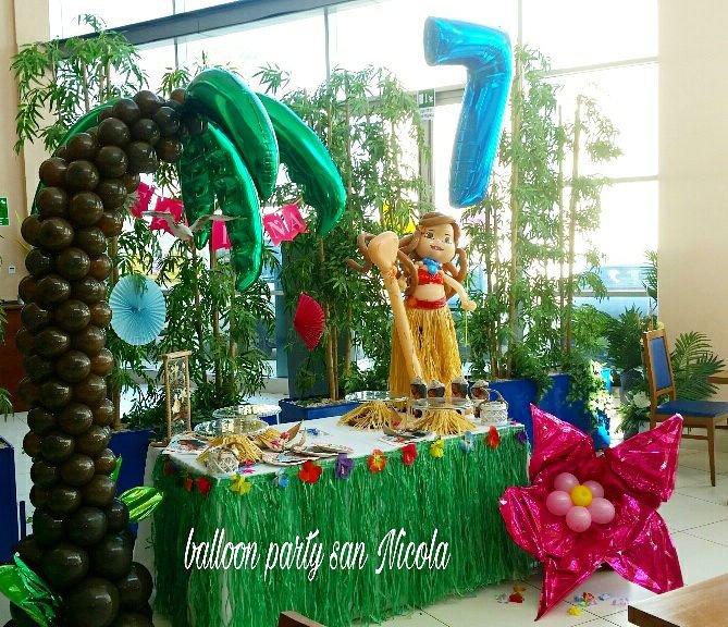 una palma artificiale, un tavolo verde con degli oggetti, un pupazzo di una donna e un fiore fucsia di gomma con delle perle