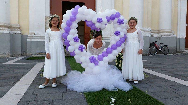 delle bambine vestite da damigelle e un cuore fatto di palloncini bianchi e viola
