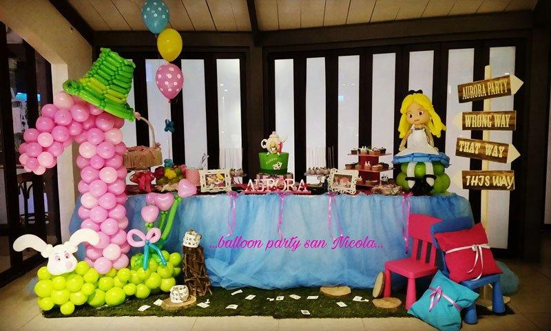 un tavolo azzurro e dei palloncini colorati con i personaggi di Alice nel paese delle meraviglie