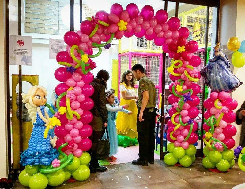 un arco fatto di palloncini fucsia con dei personaggi e delle persone in piedi