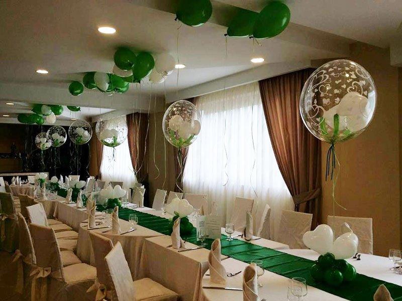 una tavolata apparecchiata per un ricevimento e dei palloncini bianchi e verdi