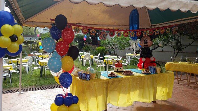 un tavolo giallo con sopra del cibo, il pupazzo di Topolino fatto di palloncini e altri palloncini