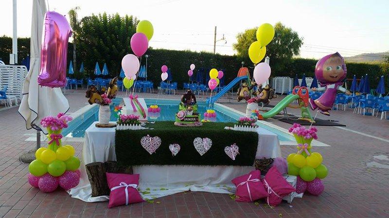 un tavolo vicino a una piscina con dei palloncini di color giallo e fucsia con dei pupazzi