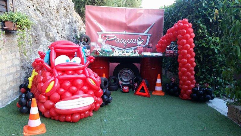 un tavolo di una festa dei compleanno e palloncini di color rosso in tema dei personaggi del cartone animato Cars