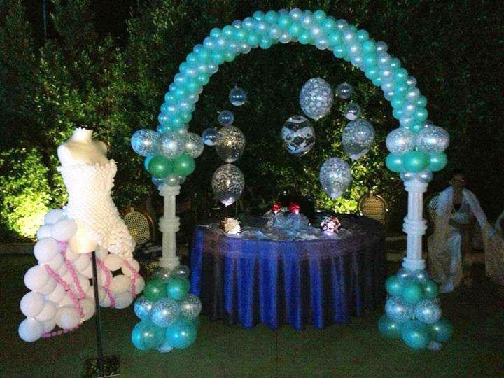 un tavolo rotondo con una tovaglia blu in un giardino, un arco di palloncini azzurri e un vestito da donna di color bianco fatto di palloncini