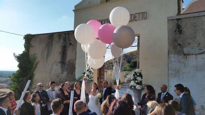 due sposi con due palloncini in mano e gli invitati attorno
