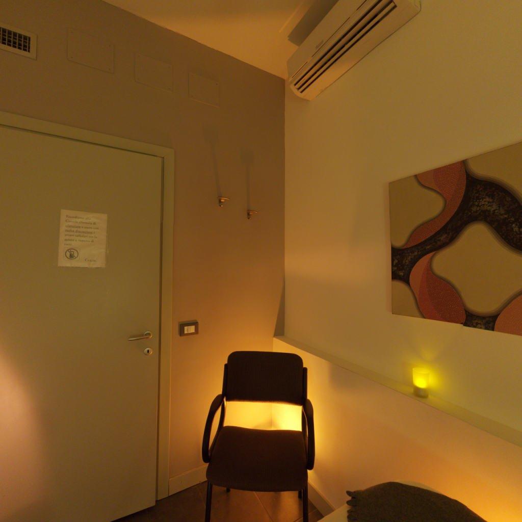 una stanza con una sedia e sulla sinistra una porta