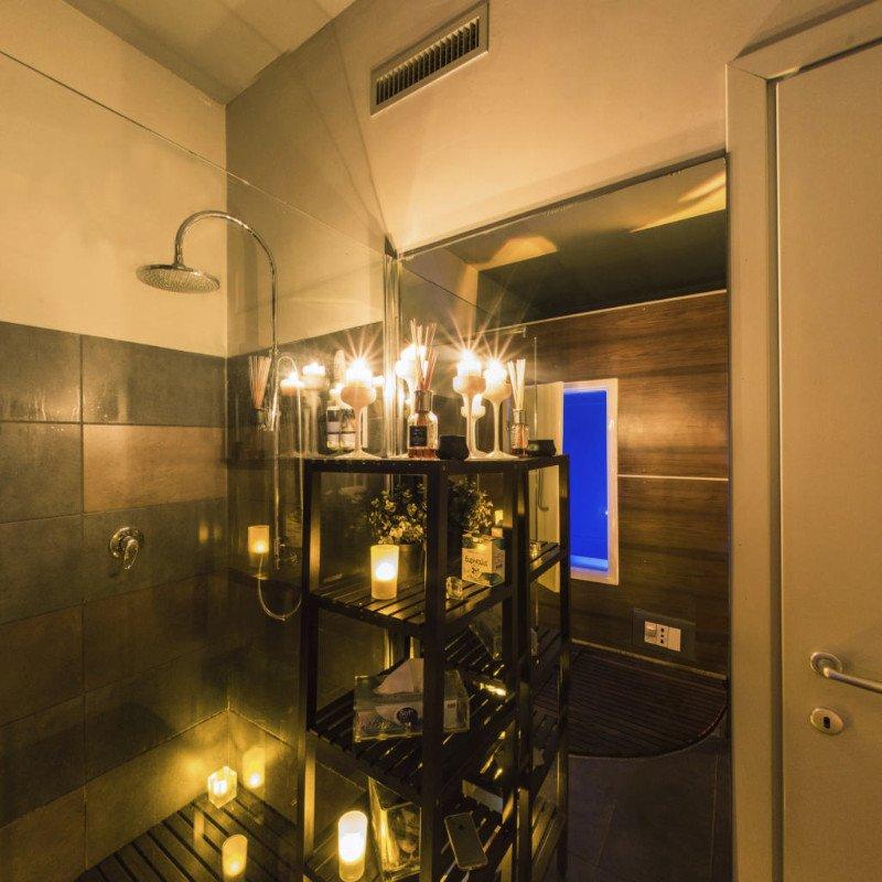 uno scaffale con delle candele accese e sulla sinistra una doccia