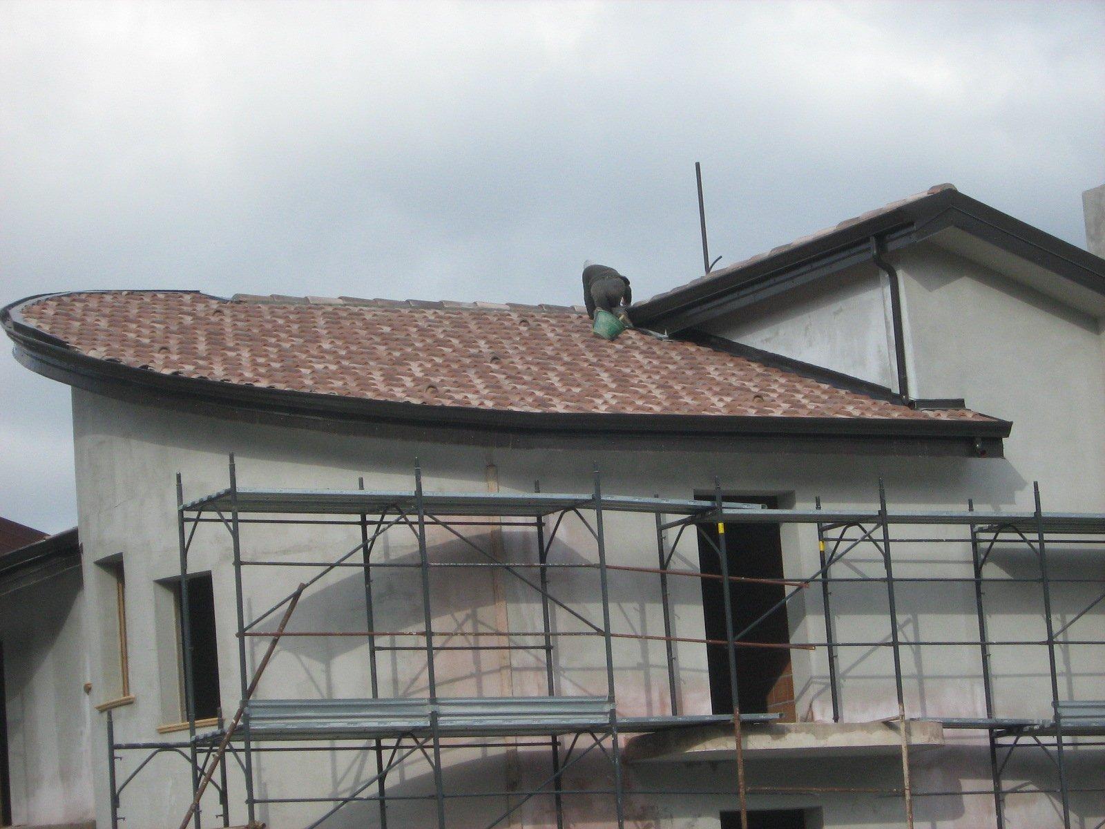 operaio sul tetto esegue un lavoro di ristrutturazione