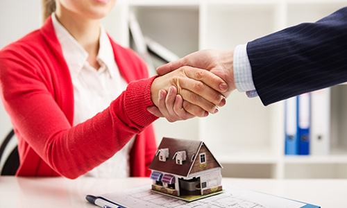 Insurance agent shaking hands with the client after home insurance deal in Caliente, NV