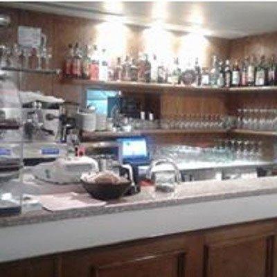 Un bancone del bar con vista degli scaffali con delle bottiglie di liquore