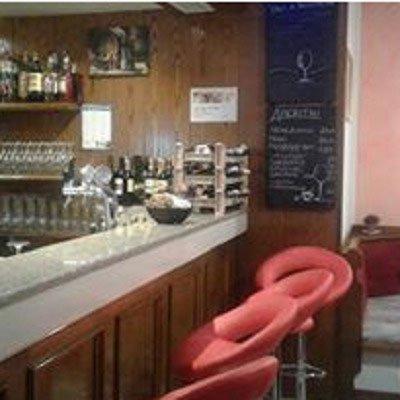 Un bancone del bar con davanti delle sedie del bar di color rosso