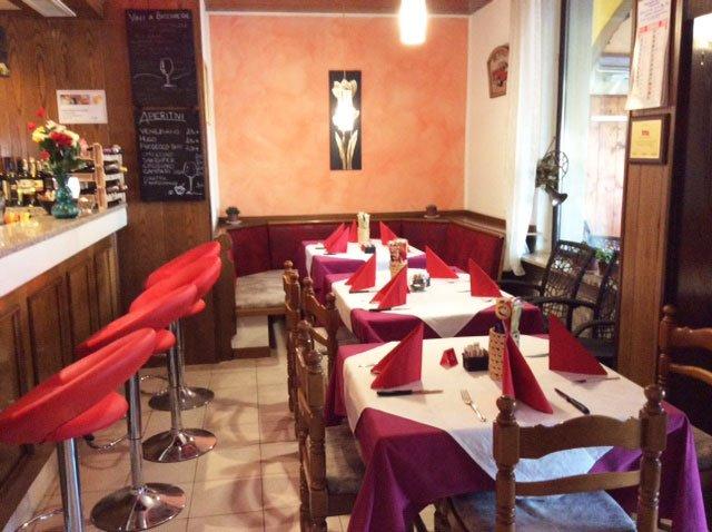 Due tavoli con tovaglie bianche e rosse all'interno di un ristorante