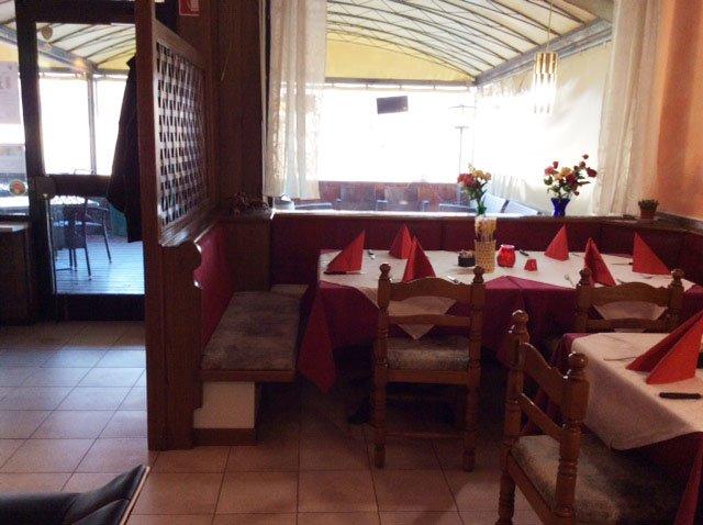 Vista dei tavoli apparecchiati all'interno e all'estero di un ristorante