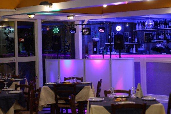 vista dei tavoli e angolo bar con delle luci accese