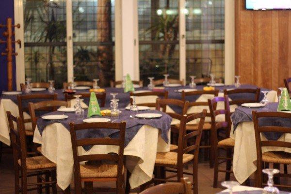 interno di un ristorante con tavoli con tovaglie blue e bianche
