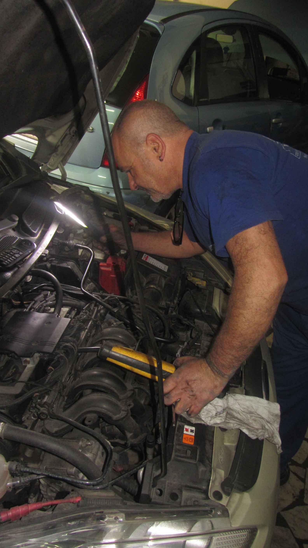 Meccanico ispeziona motore di un'auto