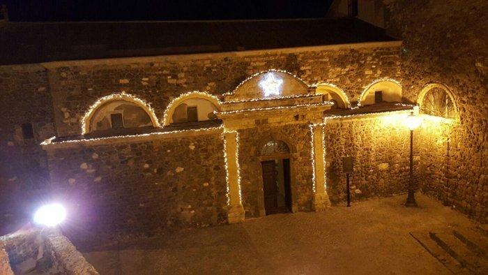 Facciata edificio storico con luminarie natalizie a Castelsardo