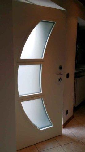 una porta bianca in legno con tre vetrate