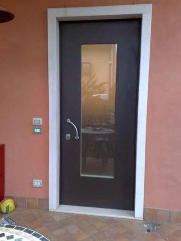 una porta in legno nero con un vetro al centro