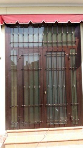 una serranda anti intrusione e dietro una finestra in legno