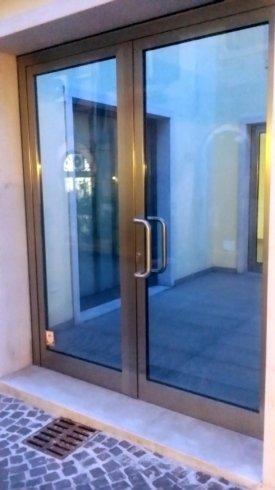 una porta in vetro con finiture in ferro