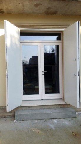 due ante in ferro bianco spalancate e dietro una porta in pvc bianco