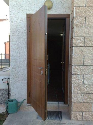 una porta in legno marrone semi aperta
